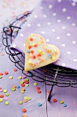A heart-shaped biscuits with colourful sugar sprinkles