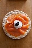 A cracker topped with smoked salmon, sour cream and caviar