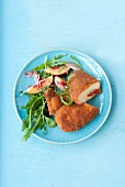 Fried chicken filled with camembert and sausage and a peach and rocket salad