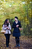 Two women collect mushrooms in an autumnal forest