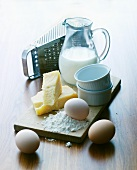 An arrangement of souffle ramekins, eggs, cheese, a cheese grater and milk