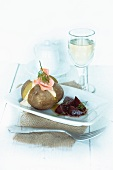 A baked potato with a sour cream dip, salmon and beetroot