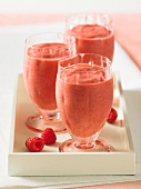Three raspberry and cranberry smoothies on a tray