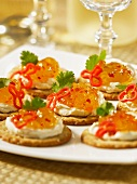 Crackers topped with pineapple and habanero jelly