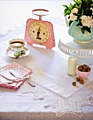 A cup of tea, an old pair of kitchen scales, a bunch of flowers, coffee cream and brown sugar