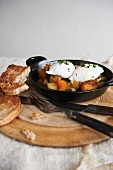 Poached Eggs Over Hash in a Cast Iron Skillet; Toast