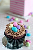 A red velvet cupcake with chocolate cream and sugar eggs