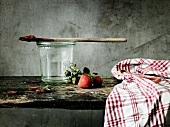 Weckglas, Holzlöffel, Küchentuch und Erdbeeren auf Holzbrett