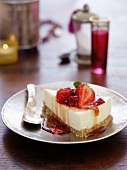 A slice of cream cheese cake with strawberries