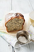 Lemon and poppy seed cake and icing sugar in a sieve