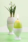 Snow drops in Easter egg and egg-shaped candle