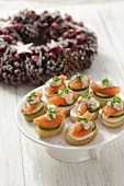 Potato slices topped with egg, cucumber and smoked salmon for Christmas