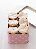 Mince pies dusted with icing sugar in a tin