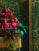 A multi-layer chocolate cake decorated with fresh red berries and biscuits