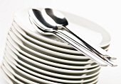 Stacked Plates with Spoons; White Background
