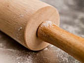 Wooden Rolling Pin with Flour on a Steel Surface