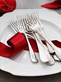 Weisser Teller mit Gabeln und rotem Geschenkband