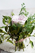 A small bouquet of a rose, mistletoe and conifers