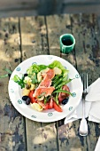 A mixed leaf salad with sliced salmon