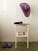 Stummer Diener in Stuhlform mit lässigem Filzhut auf Rückenlehne und Bücher auf Ablagen