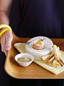A woman holding a tray with a boiled egg and soldiers