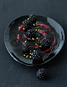 Blackberries with fruit sauce and chopped pistachios