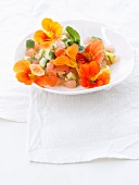 Mango and grapefruit salad with avocado and nasturtium flowers