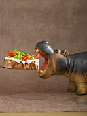 Toast topped with mayonnaise and vegetables with a hippo figurine