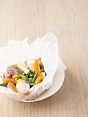 Andouillette with spring vegetables in parchment paper