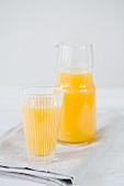 Orange juice in a glass and in a carafe