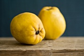 Two quinces on a wooden board