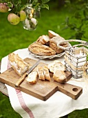 A baguette on a chopping board and other types of bread in a bread basket on a table in the open air