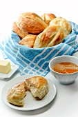 Basket of Bolillo Rolls; One on a Plate Halved; Honey in a Bowl