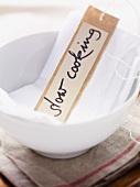 Kärtchen mit 'Slow Cooking' Aufschrift in einem Schälchen