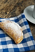An apple turnover dusted with icing sugar on a checked cloth