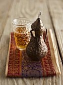 Black tea in an oriental jug and a glass