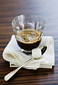 A glass of espresso with a lump of sugar