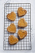 Decorated heart-shaped cinnamon biscuits on a wire rack