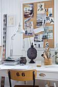 Schreibtisch mit Schreibtischlampe vor Pinnwand an weisser Holzwand