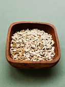 A wooden bowl of spelt flakes