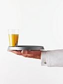 Waiter holding a tray with a glass of orange juice