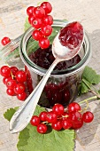 A glass of red currant marmalade and fresh red currants