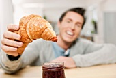 A man eating a croissant with jam