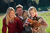 Family in a meadow with live hen