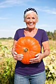 A woman in a field holing a giant pumpkin