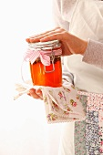 A woman holding a jar of rose jelly