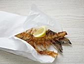 Frittierte Fischgräten in Papiertüte