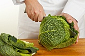 A savoy cabbage being cut in half