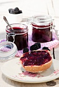 A bread roll spread with blackberry jelly