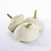 Three white pattypan squashes